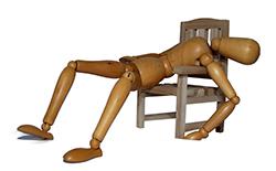 wooden mannequin asleep on chair)